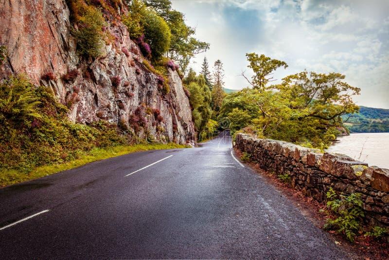 Дорога пропуска Kirkstone с скалистой горой на левой и каменной стене на праве стоковая фотография