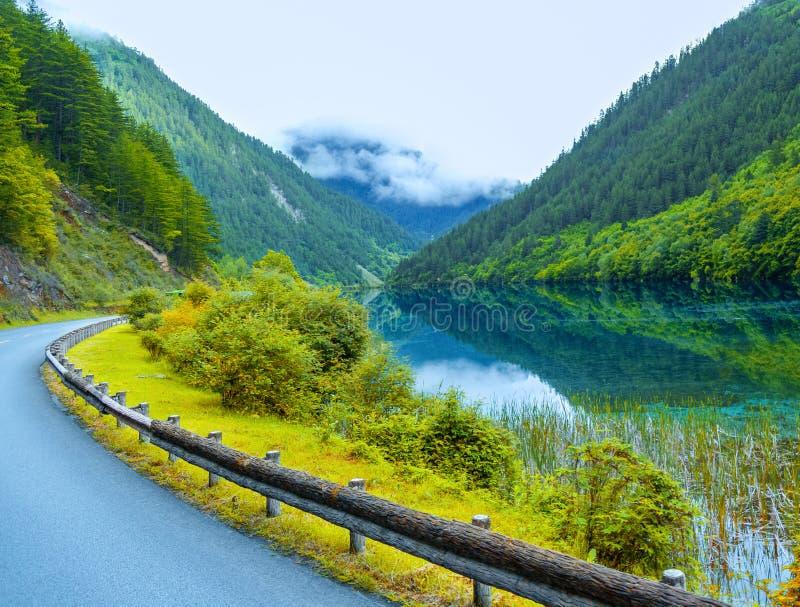 Дорога протягивает вне от гор Далекие горы были положены в кожух в озеро тумана рядом с ним отражают зеленые горы стоковое изображение