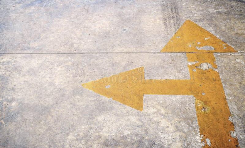 Дорога с желтой стрелкой на конкретной предпосылке стоковые фото