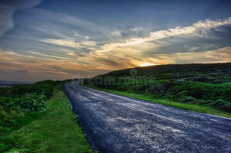 Дорога с загибом к заходу солнца стоковое фото