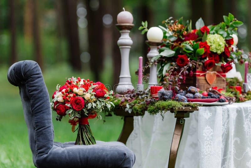 Дорогой, ультрамодный букет свадьбы роз в marsala и красные цвета стоя на стуле Bridal детали и оформление с цветками стоковые изображения rf
