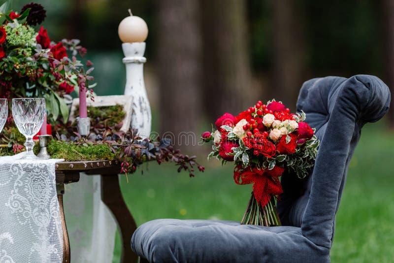 Дорогой, ультрамодный букет свадьбы роз в marsala и красные цвета стоя на стуле Bridal детали и оформление с цветками стоковая фотография
