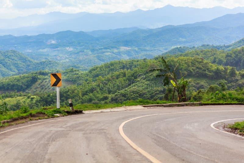 Дорожные знаки изгибают правильное направление на шоссе горы, предупреждая аварию стоковые фотографии rf