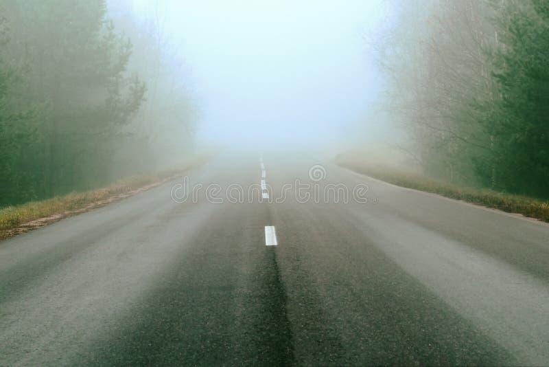 Дорожные разметки и линии Туман покрывает часть дороги путешествовать далеко для длинных расстояний Шоссе в естественном ландшафт стоковые фотографии rf