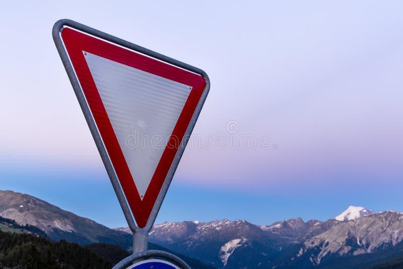 Дорожный знак дает путь высокогорной предпосылке гор стоковые изображения rf