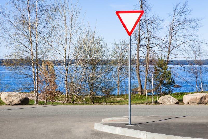 Дорожный знак - дайте путь, на предпосылке голубого озера стоковое изображение