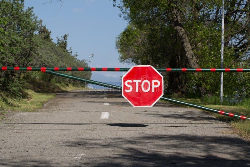Дорожный знак прикрепленный к барьеру стоковые изображения