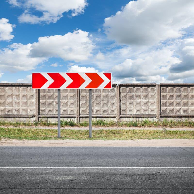Дорожный знак стоит около городской дороги стоковые изображения rf