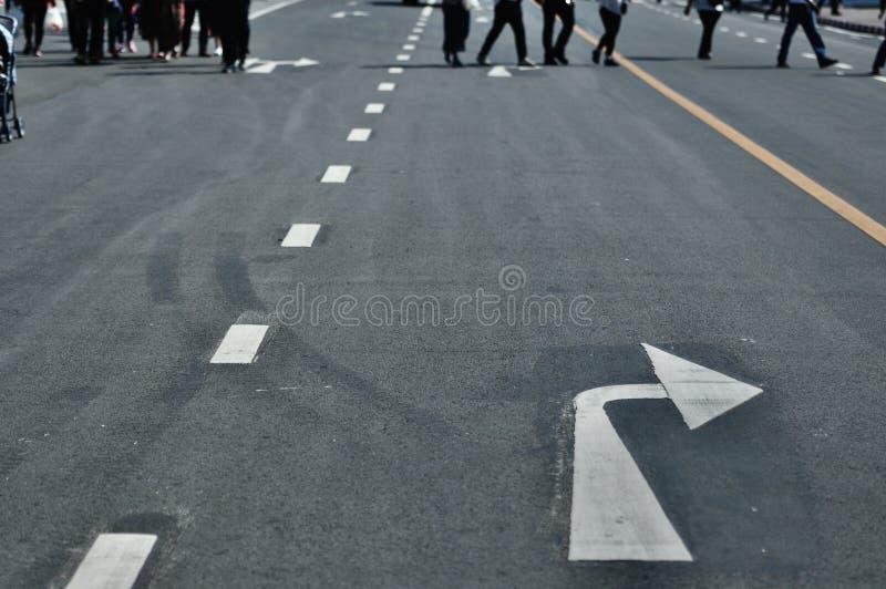Дорожный знак с 2 белыми стрелками указывая в различные левую сторону и правильное направление стоковое изображение