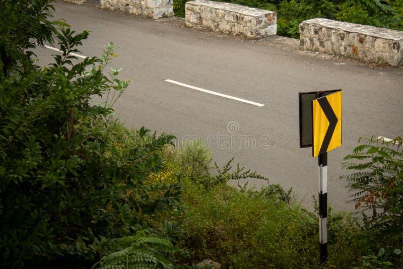 Дорожный знак, указывающий поворот вперед вдоль красивой дороги Гат на горном хребте Салем, Тамилнад, Индия стоковое фото