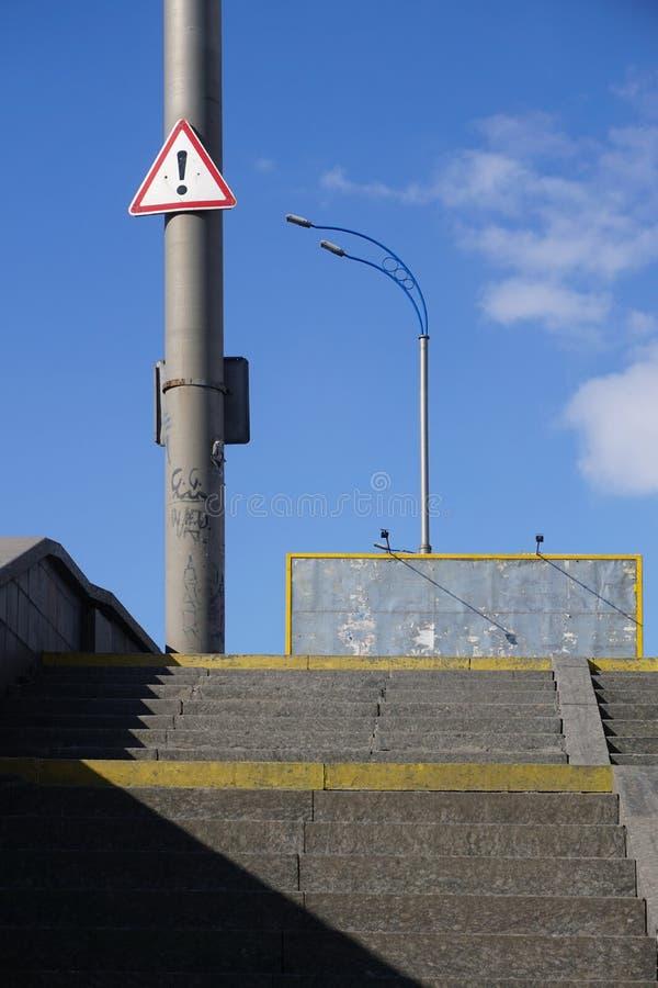 Дорожный знак - черный восклицательный знак в красной смертной казни через повешение треугольника на поляке, предупреждая о опасн стоковое изображение rf