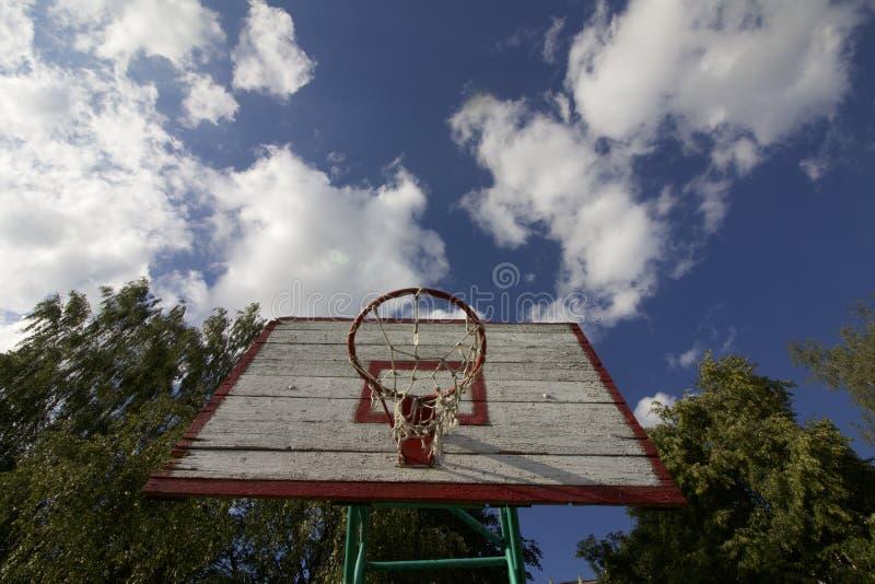 Доска баскетбола с сетью Старые, деревянные планки покрашено Размещенный на предпосылке голубого неба с облаками Игры спорта в дв стоковое фото rf