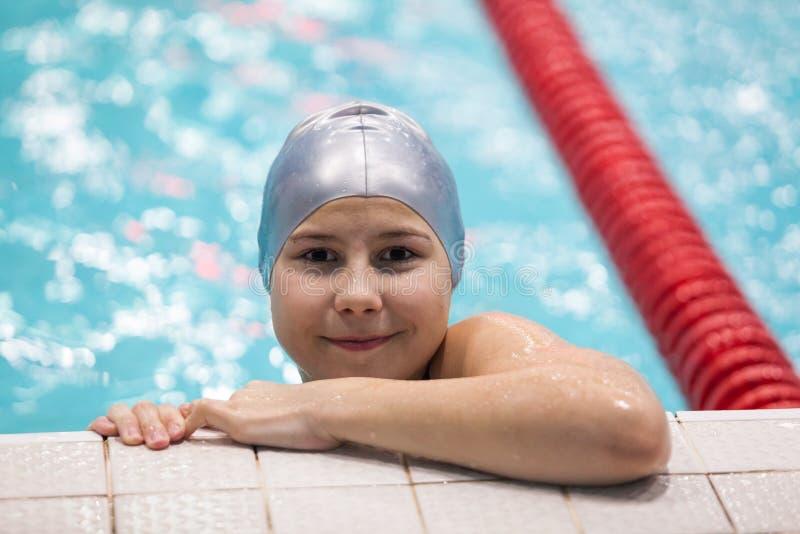 Доска в бассейне, молодой спортсмен удерживания девушки пловца на разминке стоковое фото rf