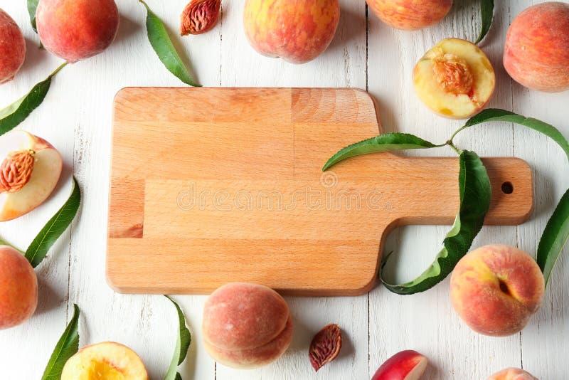 Доска и свежие персики на белом деревянном столе стоковые изображения rf