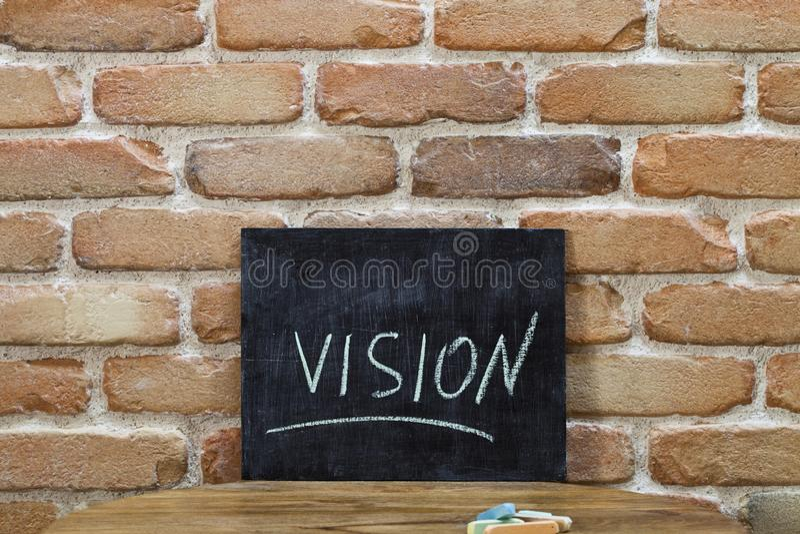 Доска мела со словом ЗРЕНИЕМ потонуть вручную и мел на деревянном столе на предпосылке кирпичной стены стоковое фото