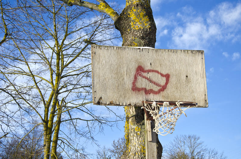 Доска обруча баскетбола примитивная с сломленной сетью на дереве стоковая фотография rf