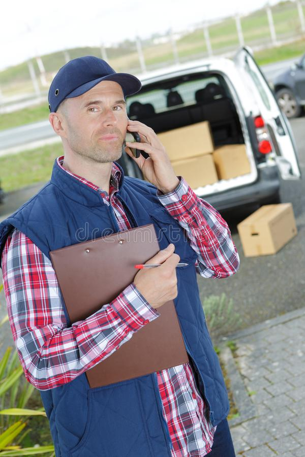 Доска сзажимом для бумаги работника доставляющего покупки на дом holiding и говорить на телефоне стоковые изображения