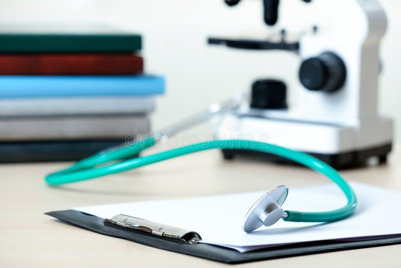 Доска сзажимом для бумаги с отчетом и стетоскоп на таблице стоковое фото