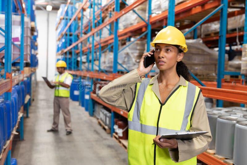 Доска сзажимом для бумаги удерживания женского работника и говорить на мобильном телефоне в складе стоковое фото
