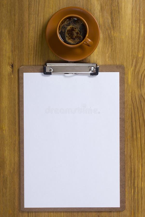 Доска сзажимом для бумаги и кофейная чашка стоковые фотографии rf