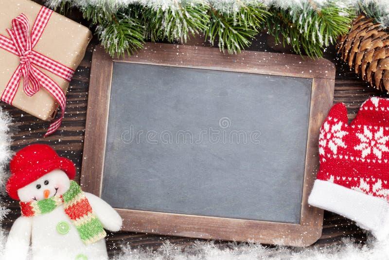 Доска, снеговик и ель рождества стоковое фото rf