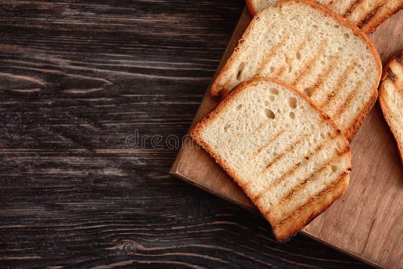 Доска с вкусным провозглашанным тост хлебом на деревянной предпосылке, взгляде сверху стоковое фото