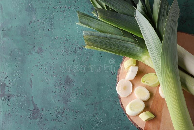 Доска с отрезанным сырцовым лук-пореем на таблице стоковое фото rf