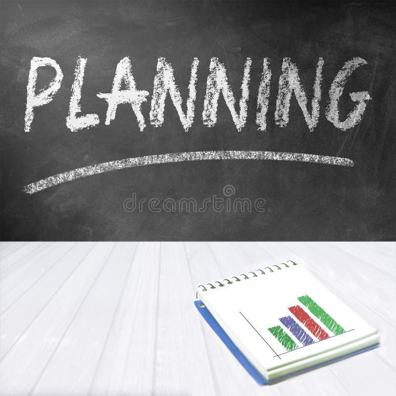 Доска с планированием слова написанным дальше Тетрадь с финансовой диаграммой стоковые изображения rf