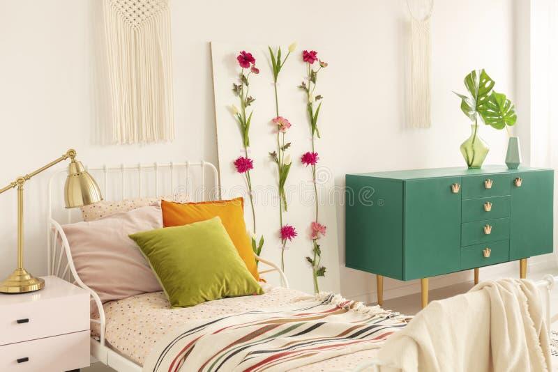 Доска цветка между односпальной кроватью с прованскими зелеными, оранжевыми и пастельными розовыми подушками и зеленым деревянным стоковые фотографии rf