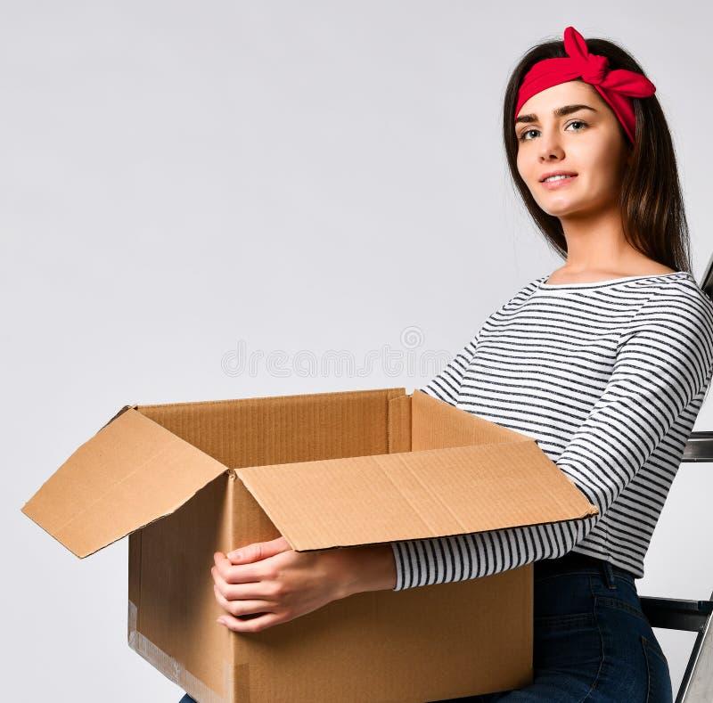 Доставка, перестановка и распаковывать Усмехаясь картонная коробка удерживания молодой женщины изолированная на белой предпосылке стоковое изображение rf