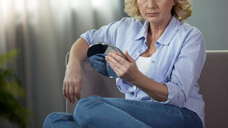 Достигшая возраста белокурая дама касаясь ее стороне смотря в зеркало руки, процесс старения стоковое изображение