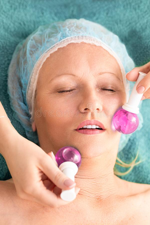 Достигшая возраста женщина в массаже обработки салона красоты с холодные стеклянные шарики Подмолаживание и skincare стоковая фотография rf