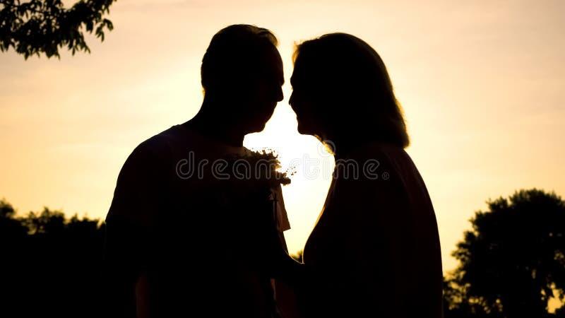 Достигшие возраста женатые пары целуя в парке сумерек, держа цветки, романтичный подарок стоковые фотографии rf