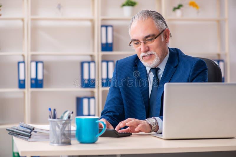 Достигший возраста мужской работник работая в офисе стоковое изображение rf