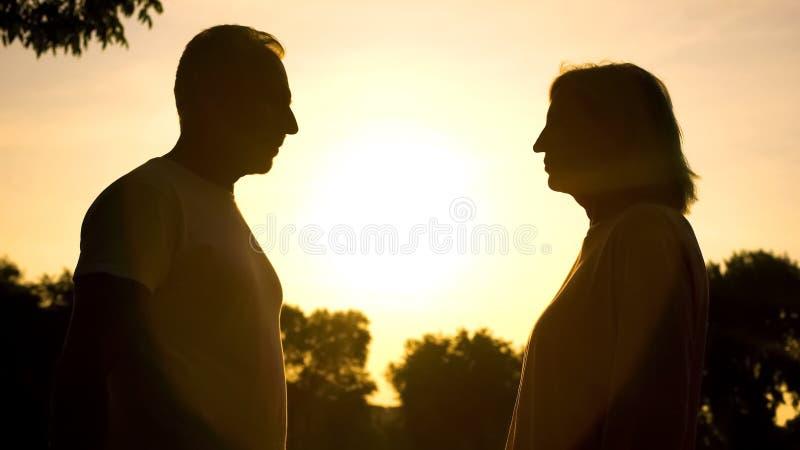 Достигший возраста мужчина и женские тени смотря один другого на заходе солнца, романтичной встрече стоковое изображение