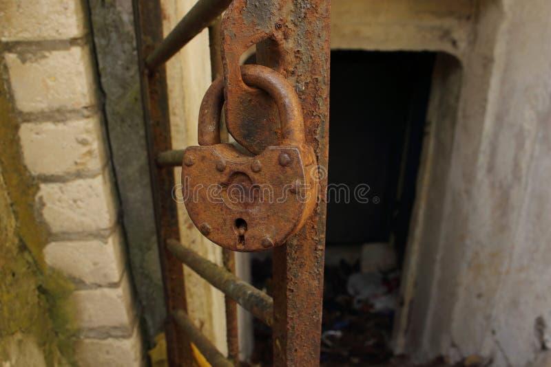 Достигший возраста ржавый замок металла вися на двери металлического стержня к получившемуся отказ укрытию бомбы стоковые фото