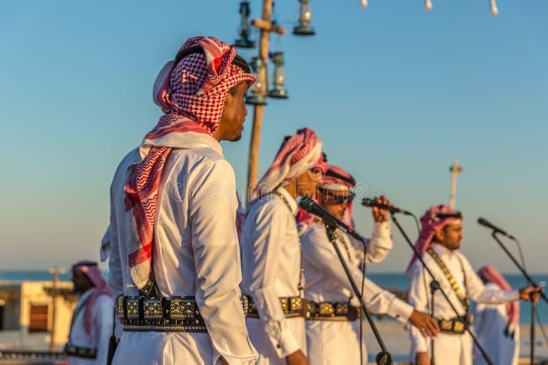 Доха, Катар, 9-ое января 2018 - красочное торжество в Дохе, при местные люди одетые с традиционными одеждами, день голубого неба, стоковое изображение rf