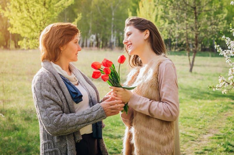 Дочь дает ей тюльпаны матери Настоящий момент дня ` s матери стоковые фотографии rf