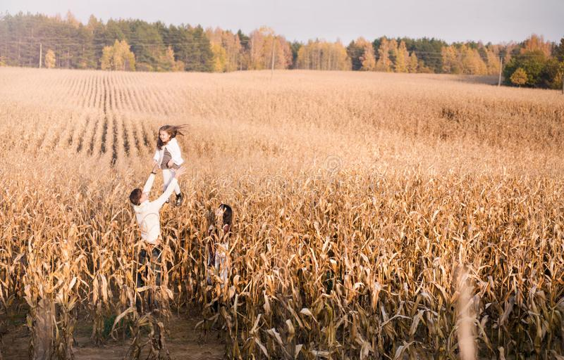 Дочь броска папы вверх в кукурузном поле осени стоковые изображения