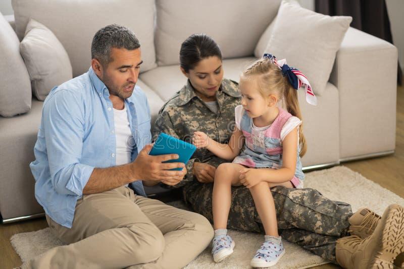 Дочь взволнована перед тем, как посмотреть мультфильм с папой и мамой стоковое изображение