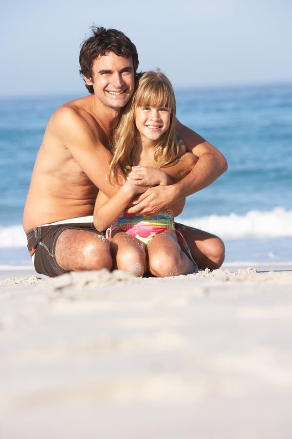 дочь вниз будет отцом сидя носить swimwear стоковая фотография