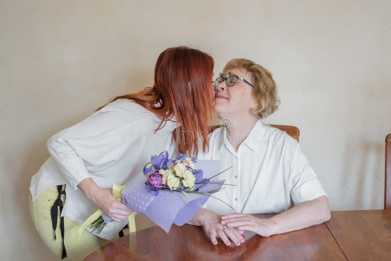 Дочь давая цветки взрослой матери Дочь давая цветки для того чтобы быть матерью и целуя ее на щеке Тратящ время совместно, стоковое изображение