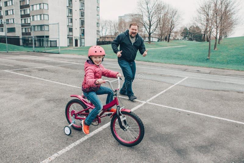 дочь девушки порции тренировки отца для того чтобы ехать велосипед стоковое фото rf