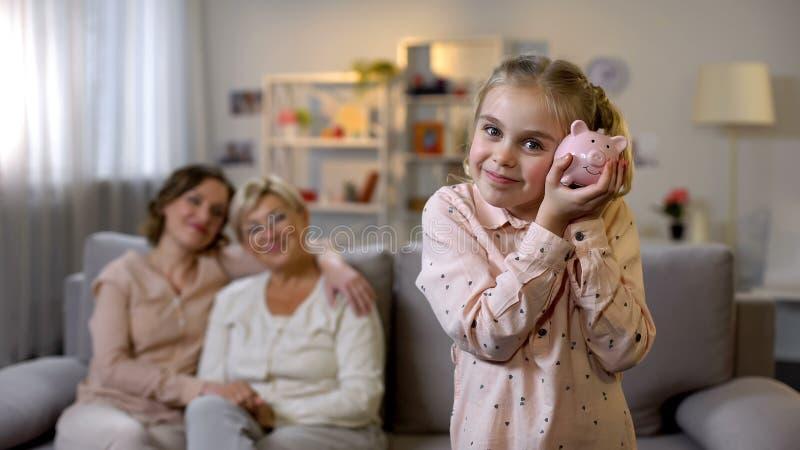 Дочь держа piggybank, мать и бабушка позади, учащ, что сохранило деньги стоковые фотографии rf