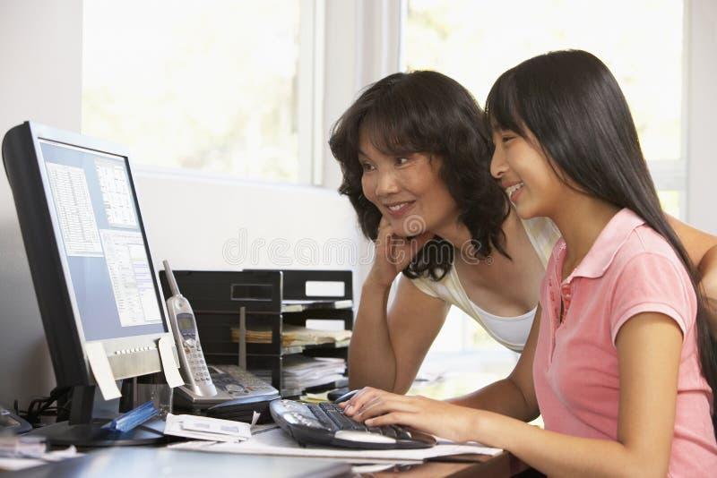 дочь компьютера подростковая используя женщину стоковое фото