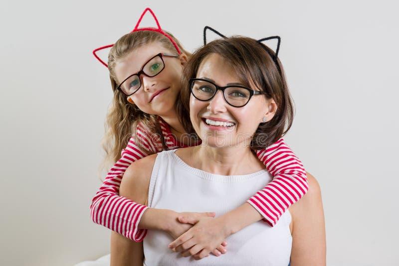 Дочь любяще обнимает ее мать Родитель и ребенок в стеклах стоковая фотография
