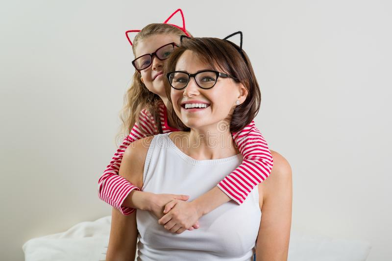 Дочь любяще обнимает ее мать Родитель и ребенок в стеклах стоковые изображения
