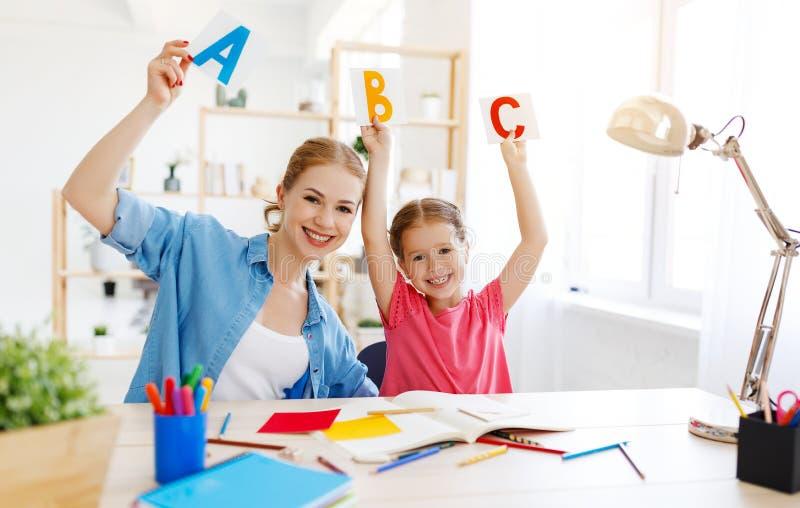 Дочь матери и ребенка делая сочинительство домашней работы и читая дома стоковая фотография rf