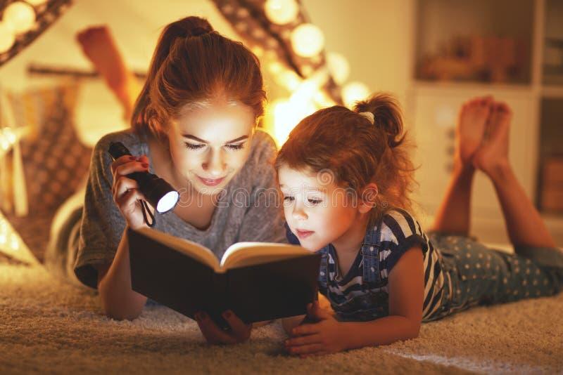 Дочь матери и ребенка читая книгу и электрофонарь раньше стоковые фотографии rf