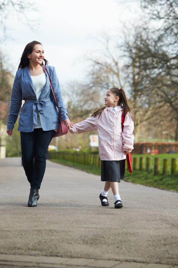 Дочь матери идя к школе вдоль пути стоковое изображение rf